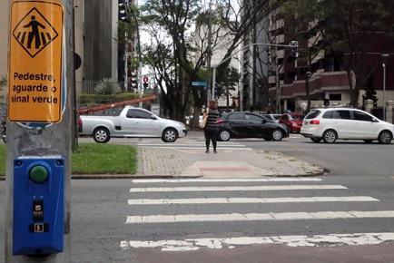 Faixa de pedestres com o botão de pedestres em primeiro plano