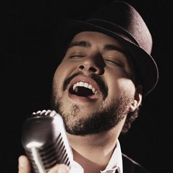 Tiago está em close, usando um chapéu e cantando de olhos fechados