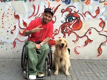 Rapper Billy está em sua cadeira de rodas, ao lado de um cão
