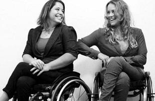 Duas mulheres cadeirantes se olham sorrindo
