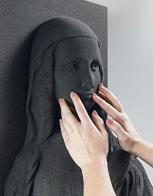Mãos femininas em close tocam o rosto de Mona Lisa impressa em 3D