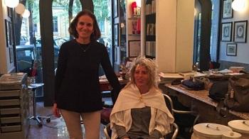 Tiziana está em pé ao lado de uma cliente sentada na cadeira do salão