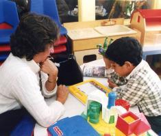 Professora brinca com aluno em sala de aula