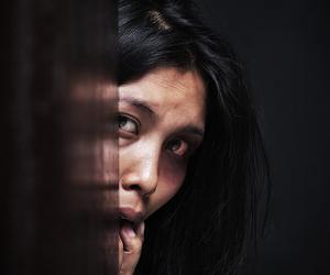Mulher acuada, escondida atrás de uma parede