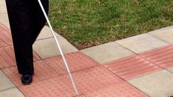 Pernas de uma pessoa andando sobre piso tátil, usando bengala