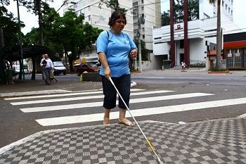 Mulher com deficiência visual atravessa a rua pela faixa.