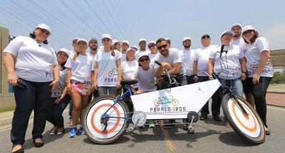 Diversas pessoas posam atrás de uma bicicleta adaptada dos pedaleiros
