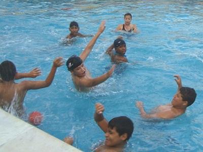 Sete alunos brincam com uma bola na piscina