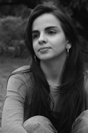 Andreza está sentada abraçando os joelhos, em imagem em preto e branco