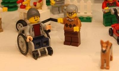 Boneco de lego em cadeira de rodas, ao lado de um boneco idoso