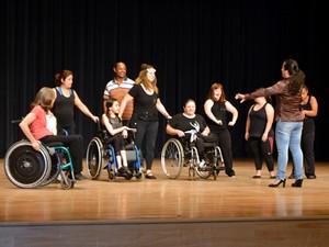 Pessoas com e sem deficiência estão em cima de um palco