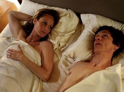 Um homem e uma mulher deitados na cama. O homem tem deficiência física