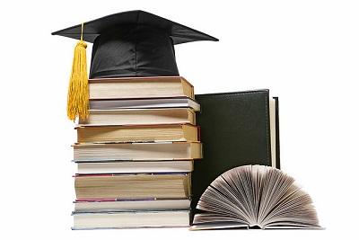 Pilha de livros com um capelo de formatura