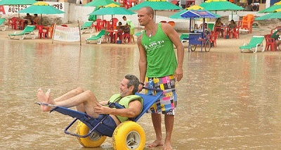 Praia de Natal com cadeirante em cadeira adaptada ao lazer à beira mar