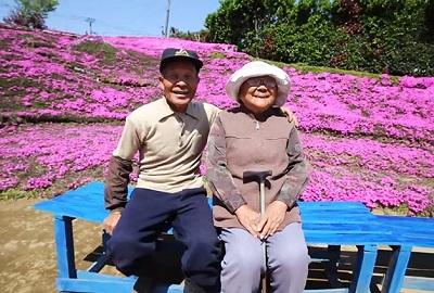 Kuroki está ao lado de sua mulher, diante de inúmeras flores rosadas