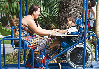 Mãe brinca com filho cadeirante em parque inclusivo