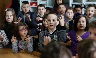 Diversas crianças usam língua de sinais. Zejd está ao centro.
