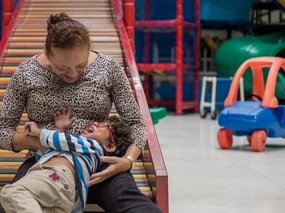 Sala com vários brinquedos. Mãe faz cócegas em criança com deficiência