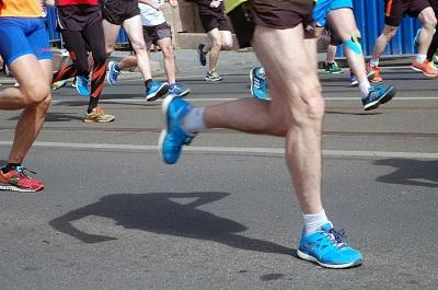 Vários pés e calçados de corredores em movimento correm na rua