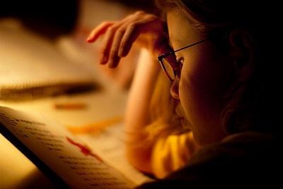 Criança usando óculos lê um livro