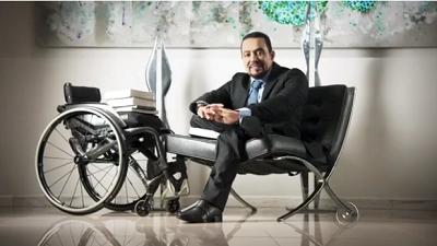 Paulo está sentado em uma poltrona, ao lado de sua cadeira de rodas