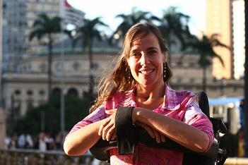 Mara Gabrilli está de rosa, sorrindo para a câmera em ambiente externo