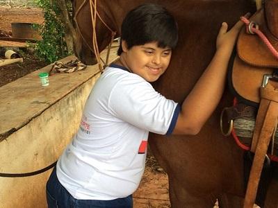 Menino com Síndrome de Down abraça um cavalo marrom