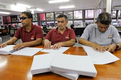Colaboradores cegos do Serviço de Impressão em Braile revisam material