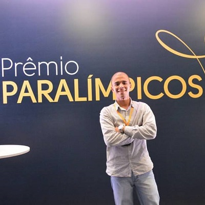 O criador do portal, Nataniel Souza, em frente à parede azul