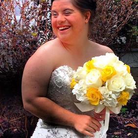 Moça com Síndrome de Down vestida de noiva e segurando buquê