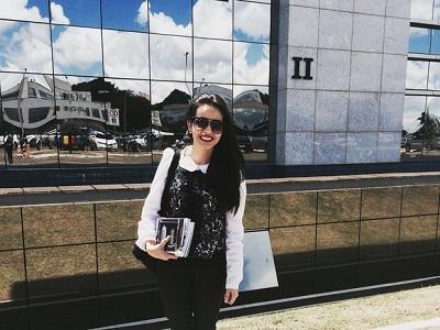 Caroline está em pé, em frente a um prédio espelhado