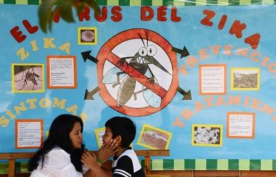 Mãe e filho abraçados em frente a painel sobre o zika, em Honduras