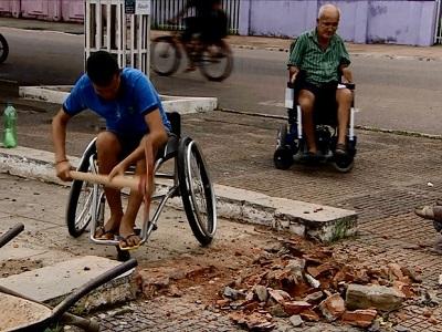Dois homens de cadeiras de rodas em um terreno em obras