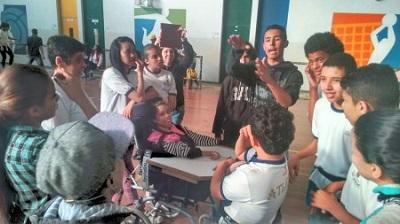 Diversos estudantes, com e sem deficiência, conversando entre si.