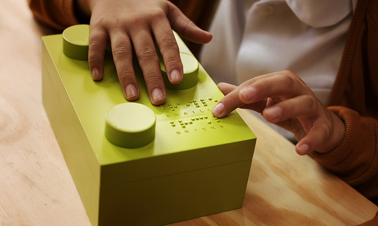 Mãos de criança tateiam um dos blocos em braile sob uma mesa de madeira