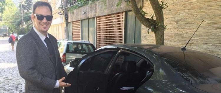 Kadu em uma rua de paralelepípedos, em frente à carro preto; ele usa óculos escuros e um blazer cinza