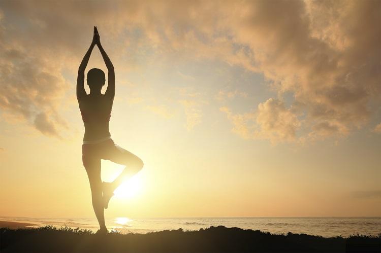 Silhueta de uma mulher jovem praticando ioga na praia com pôr do sol no horizonte