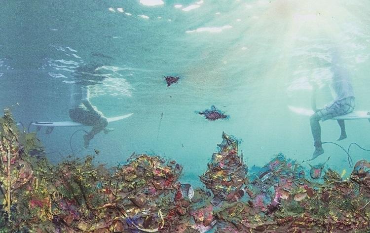 Foto do mar, com visão de duas pessoas em pranchas de surf, sentadas sobre a água; há vários objetos pintados de diferentes cores em relevo na parte debaixo da foto, como pneus , indicando que esses materiais estão no fundo do mar