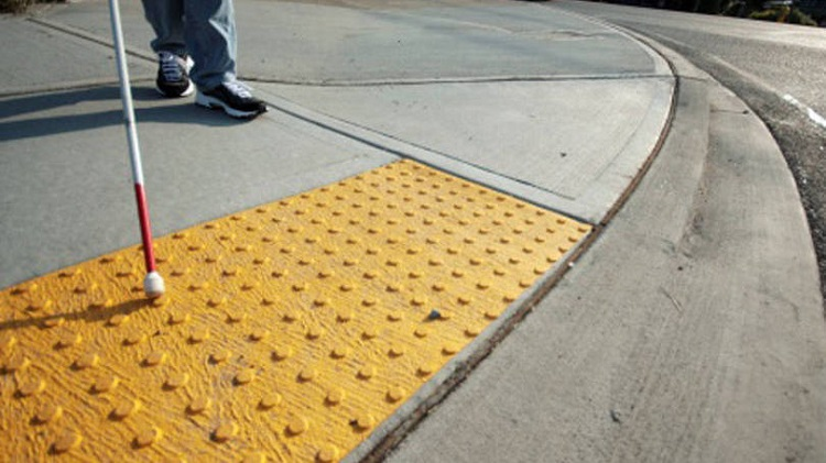 Cego com bengala em piso tátil em uma calçada