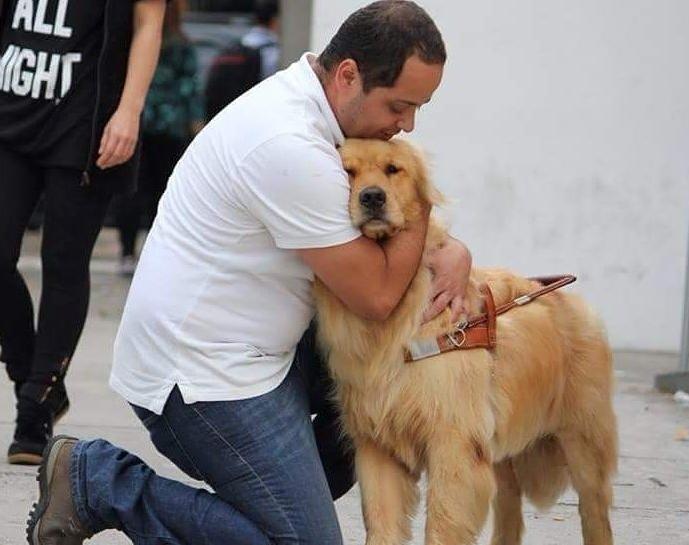 Homem está ajoelhado, abraçando um cão-guia.