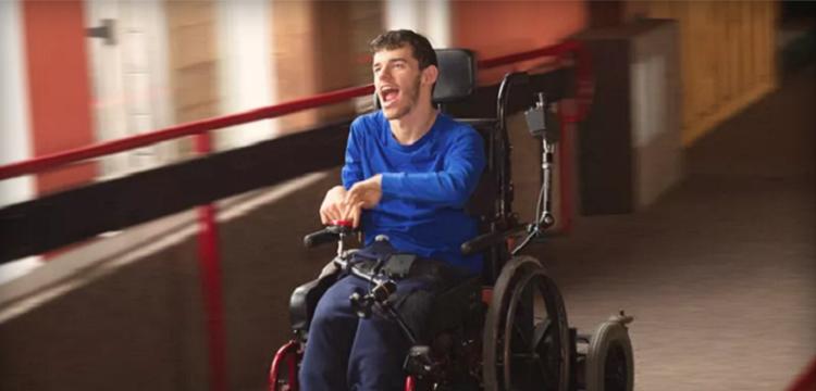 Homem jovem com deficiência em cadeira de rodas automatizada em corredor iluminado