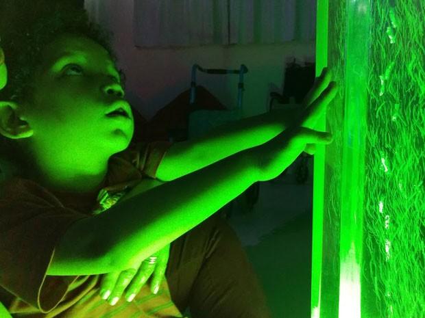 Criança toca torre borbulhante em sala com iluminação verde