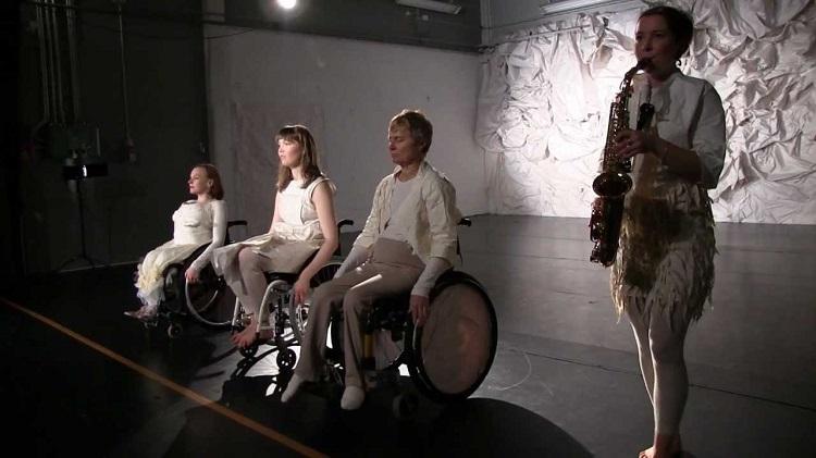 Em um palco, três cadeirantes em fila se apresentam ao lado de musicista com saxofone
