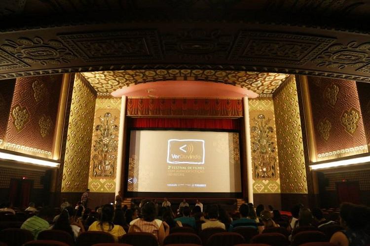 Plateia assiste a exibição de um filme em um teatro luxuoso. Na tela, está o nome do festival: Verouvindo