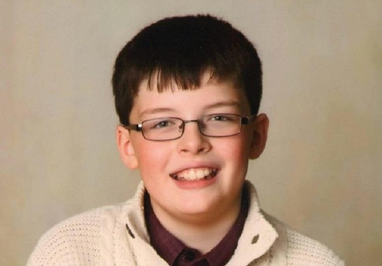 Foto de Benjamin, garoto de 10 anos; ele usa camisa vinho com um suéter branco de lã