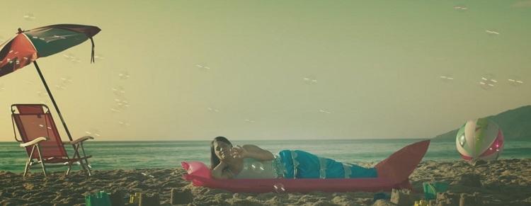 Cintia em uma praia, com guarda-sol e deitada na areia; ela usa calda de sereia e há bolhas de sabão em torno dela