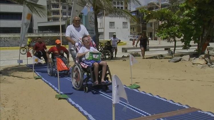 Em uma praia, um tatame de borracha forma o caminho da areia até o mar; há um jovem cadeirante sendo guiado nesse percurso por outro homem, mais velho.