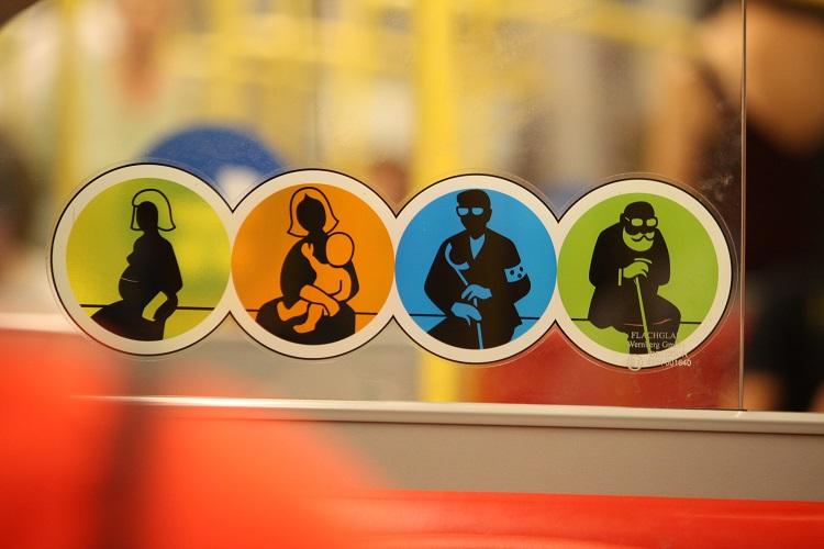 Adesivo de sinalização de assento preferencial; quatro imagens coloridas, com silhuetas dos usuários com preferência; em amarelo, uma gestante; em laranja, uma mulher com criança de colo; em azul, homem com óculos escuros e bengala, que indica deficiência visual; em verde, idoso com bengala
