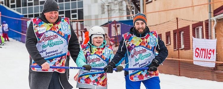 Apoiado por dois instrutores, menino com deficiência esquia