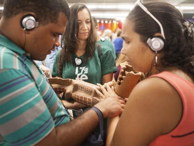 Dois visitantes cegos experimentam as peças por meio do toque e da audiodescrição.